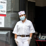 "Worker at taco restaurant in front of sign that reads ""no mask no taco"""