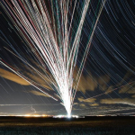 time-lapse photograph of planes at night showing many paths out of a single hub
