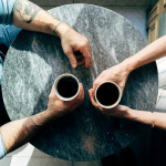 Birds-eye-view of two man drinking coffee at small table