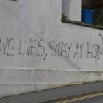 """Graffiti on a wall saying, """"Save Lives, Stay Home"""""""