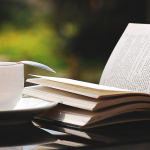 Open book with tea cup outdoors