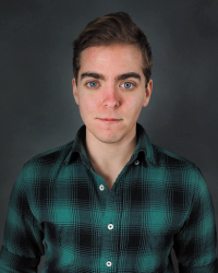 Headshot of a person wearing a plaid green and black shirt looking into the camera