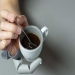 Hand with extra robotic thumb stirring coffee with a spoon